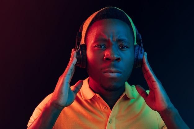 Der junge hübsche ernsthafte traurige hipster-mann, der musik mit kopfhörern an schwarz mit neonlichtern hört Kostenlose Fotos