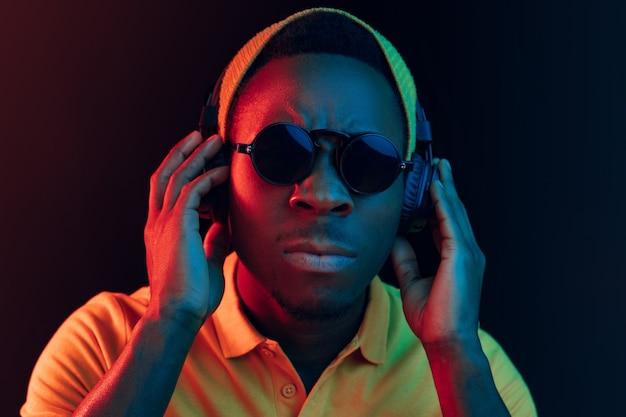 Der junge hübsche ernsthafte traurige hipster-mann, der musik mit kopfhörern im schwarzen studio mit neonlichtern hört. Kostenlose Fotos