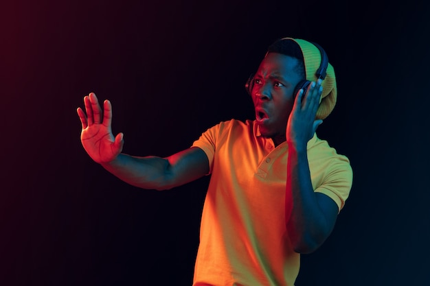 Der junge hübsche glückliche hipster-mann, der musik mit kopfhörern an schwarz mit neonlichtern hört Kostenlose Fotos