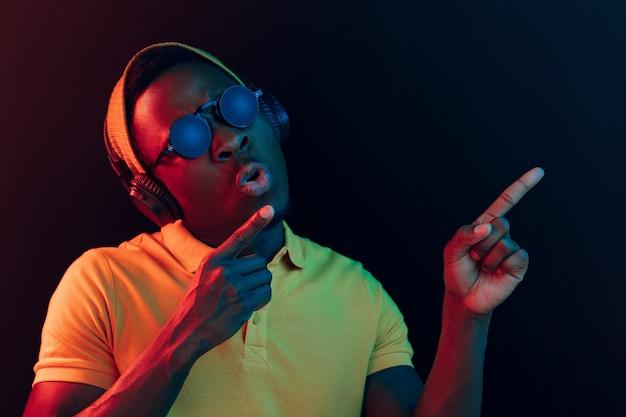 Der junge hübsche glückliche hipster-mann, der musik mit kopfhörern im schwarzen studio mit neonlichtern hört. Kostenlose Fotos