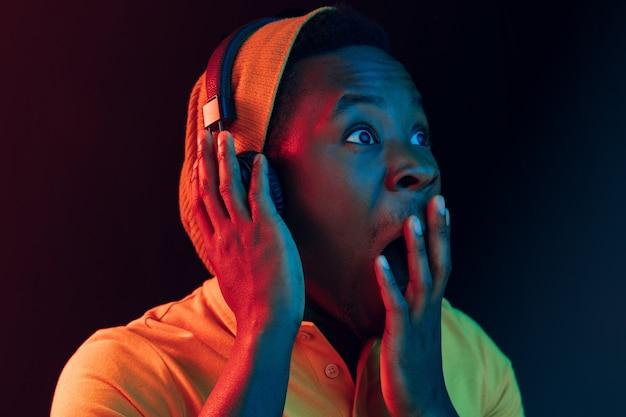 Der junge hübsche glückliche überraschte hipster-mann, der musik mit kopfhörern auf schwarz mit neonlichtern hört Kostenlose Fotos
