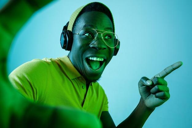Der junge hübsche glückliche überraschte hipster-mann, der musik mit kopfhörern im studio mit neonlichtern hört. Kostenlose Fotos