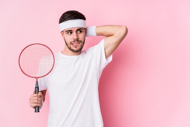 Der junge kaukasische mann, der badminton spielt, lokalisierte das berühren zurück vom kopf, dachte und traf eine wahl. Premium Fotos