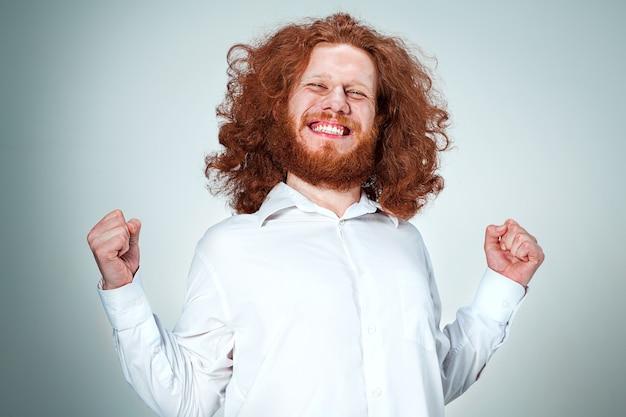 Der junge lächelnde mann mit den langen roten haaren, die