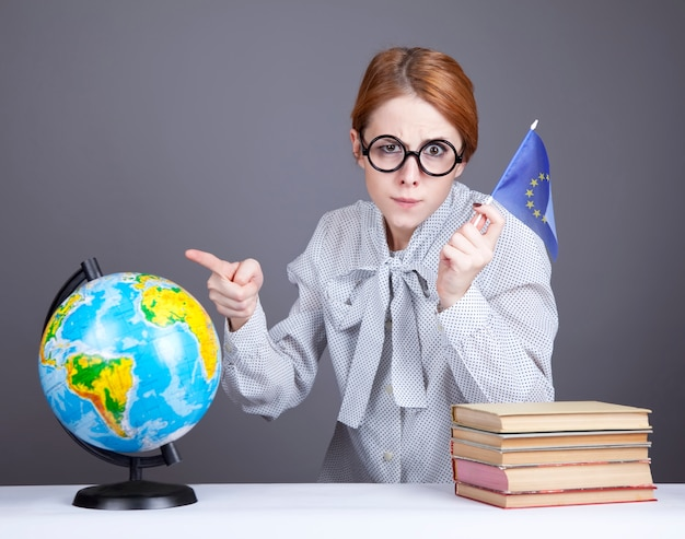 Der junge lehrer in gläsern mit büchern, globus und flagge der europäischen union. Premium Fotos