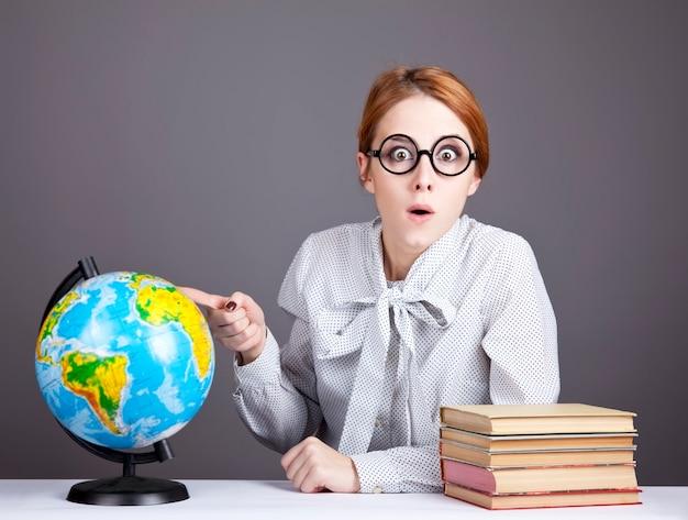 Der junge lehrer in gläsern mit büchern und globus. Premium Fotos