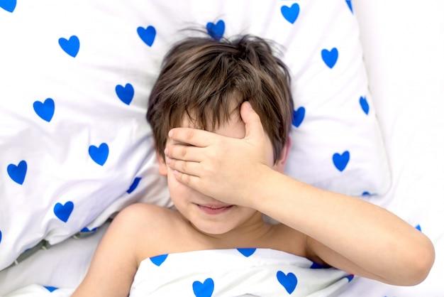 Der junge liegt mit blauen herzen in einem bett, das gesicht in den händen. emotionen ohne gesicht. weiße farbe, draufsicht Premium Fotos