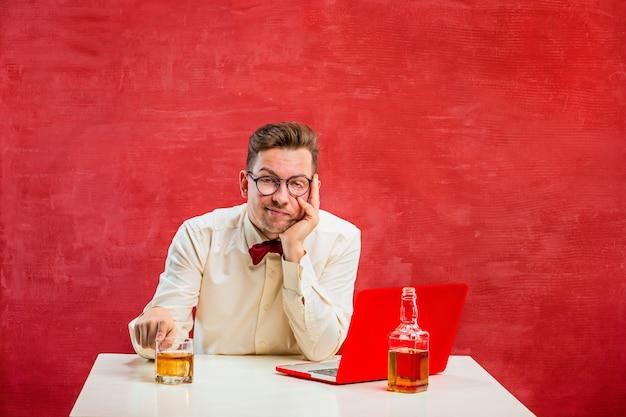 Der junge lustige mann mit cognac, der mit laptop am valentinstag auf rotem hintergrund sitzt. konzept - unglückliche liebe Kostenlose Fotos