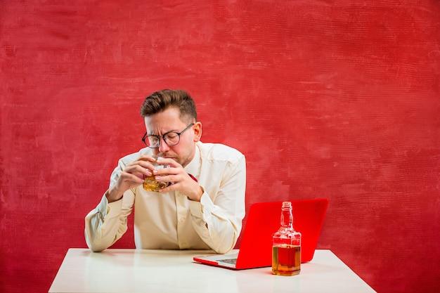 Der junge lustige mann mit cognac, der mit laptop am valentinstag auf rotem studio sitzt. Kostenlose Fotos