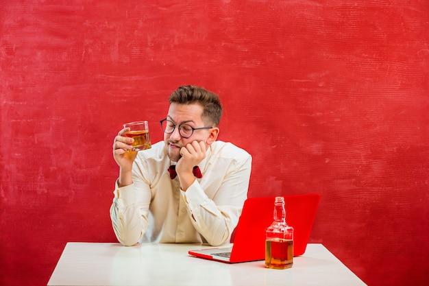 Der junge lustige mann mit cognac, der mit laptop am valentinstag auf rotem studiohintergrund sitzt. konzept - unglückliche liebe Kostenlose Fotos