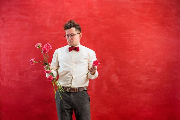 Der junge lustige mann mit gebrochenem blumenstrauß auf rotem studiohintergrund. konzept - unglückliche liebe Kostenlose Fotos