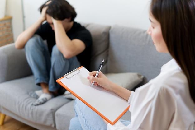 Der junge männliche patient, der auf sofa mit traurigem gesicht sitzt, hat berater durch berufspsychologenfrau. Premium Fotos