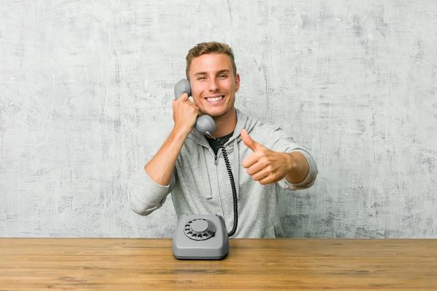 Der junge mann, der an einem weinlesetelefon mit den daumen spricht, ups, beifall über etwas, unterstützung und respektkonzept. Premium Fotos