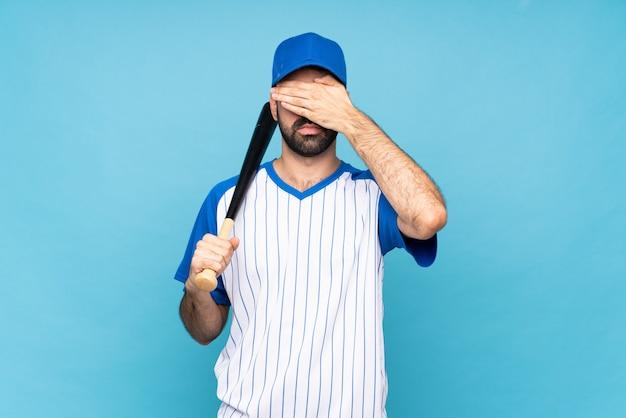 Der junge mann, der baseball über lokalisierter blauer bedeckung spielt, mustert durch hände, möchten nicht etwas sehen Premium Fotos
