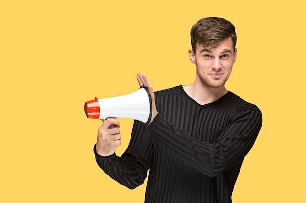 Der junge mann, der ein megaphon auf gelbem hintergrund hält Kostenlose Fotos