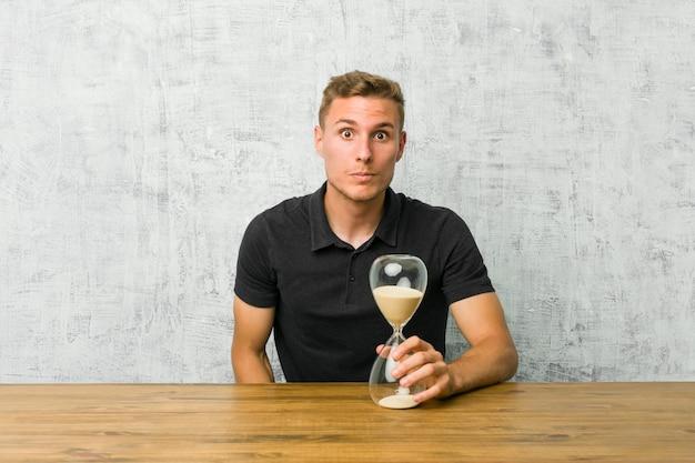 Der junge mann, der einen sandtimer auf einer tabelle hält, zuckt die schultern und die offenen augen, die verwirrt werden. Premium Fotos