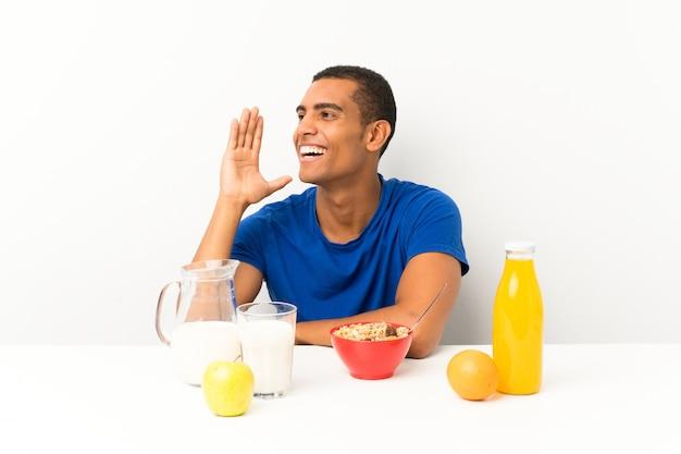 Der junge mann, der in einer tabelle schreit mit dem breiten mund frühstückt, öffnen sich Premium Fotos