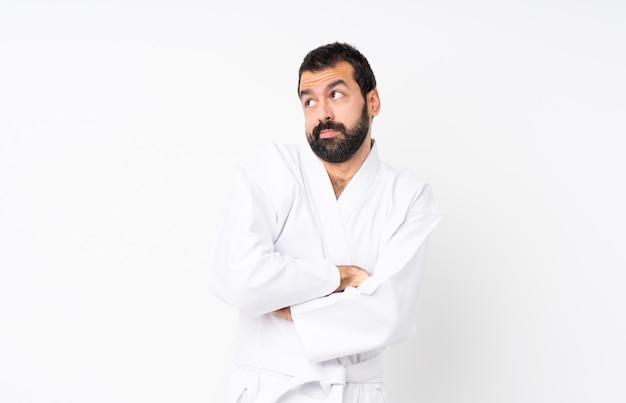 Der junge mann, der karate über lokalisiertem weiß macht zweifel tut, gestikulieren beim anheben der schultern Premium Fotos