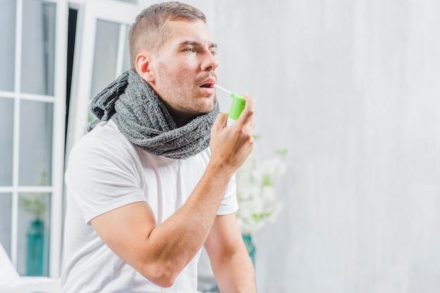 Der junge mann, der unter kälte leidet, behandelt ihren hals mit einem spray Kostenlose Fotos