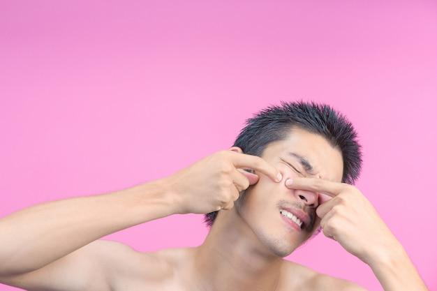 Der junge mann drückte mit den händen pickel auf sein gesicht und das rosa. Kostenlose Fotos