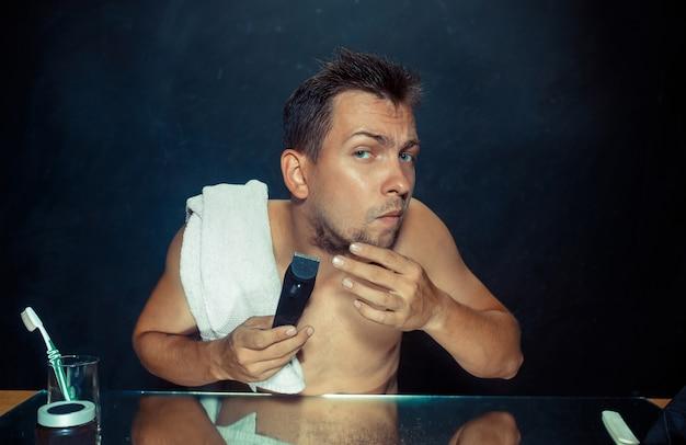 Der junge mann im schlafzimmer sitzt vor dem spiegel und kratzt sich zu hause am bart. konzept der menschlichen emotionen Kostenlose Fotos