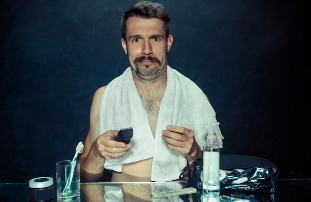 Der junge mann im schlafzimmer sitzt vor dem spiegel und kratzt sich zu hause am bart. konzept menschlicher emotionen und probleme mit der haut Kostenlose Fotos