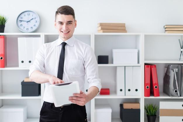 Der junge mann ist im büro und hält eine tablette. Premium Fotos