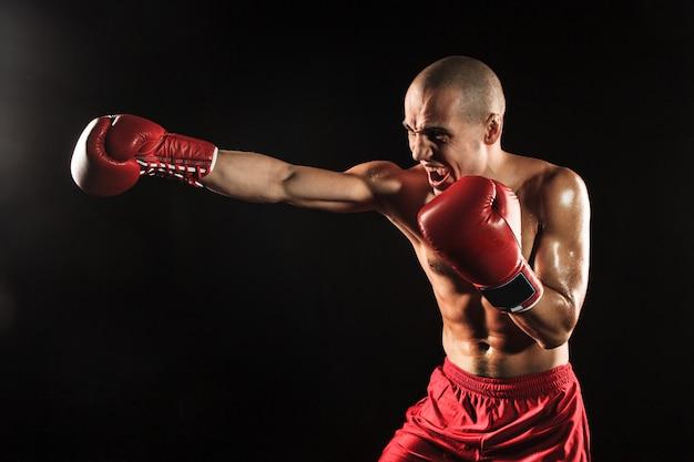 Der junge mann kickboxen auf schwarz Kostenlose Fotos
