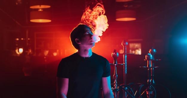 Der junge mann raucht eine shisha und stößt eine rauchwolke im shisha-raum aus Premium Fotos