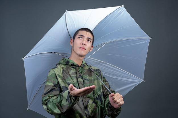 Der junge mann trägt einen tarnregenmantel und zeigt verschiedene gesten. Kostenlose Fotos