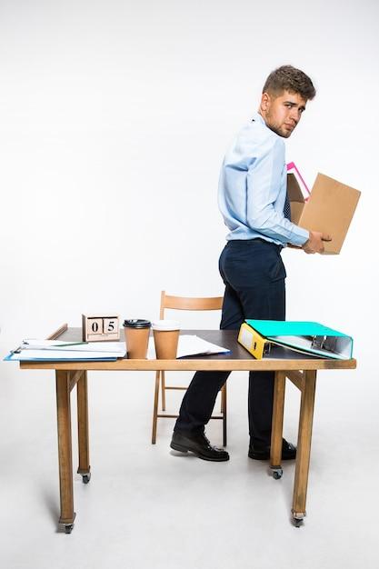 Der junge mann wird gefeuert und faltet dinge am arbeitsplatz, ordner, dokumente. konnte nicht mit verantwortlichkeiten fertig werden. konzept der probleme des büroangestellten, des geschäfts, der werbung, der rücktrittsprobleme. Kostenlose Fotos