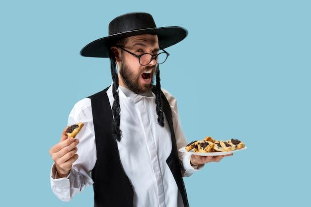 Der junge orthodoxe jüdische mann mit hamantaschen-keksen für das festival purim Kostenlose Fotos