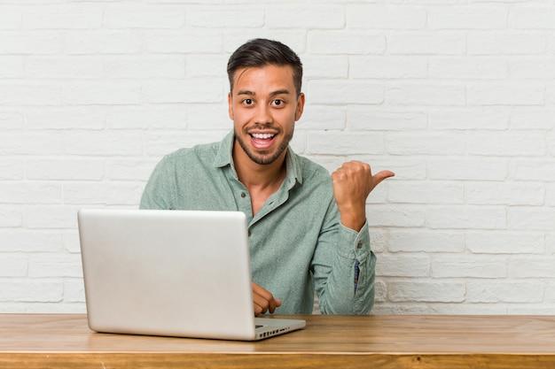 Der junge philippinische mann, der das arbeiten mit seinem laptop sitzt, zeigt mit dem daumenfinger weg, lacht und sorglos. Premium Fotos
