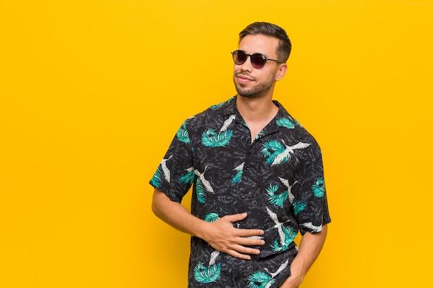 Der junge philippinische mann, der sommerkleidung trägt, berührt bauch, lächelt leicht Premium Fotos