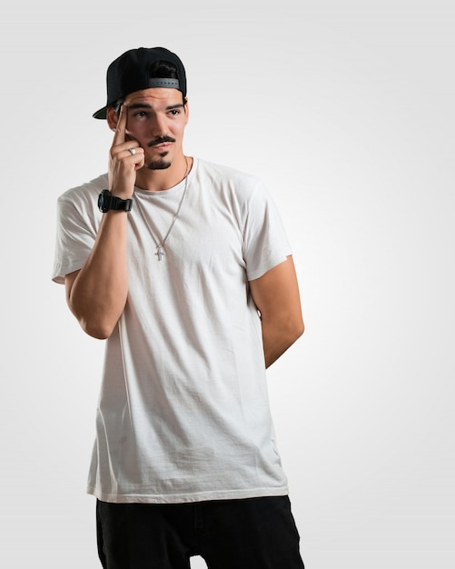 Der junge rapper-mann, der oben denkt und über eine idee verwirrt nachdenkt, würde versuchen, eine lösung zu finden Premium Fotos