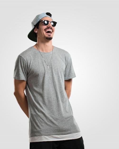 Der junge rappermann, der spaß lacht und hat, entspannt und nett ist, fühlt sich überzeugt und erfolgreich Premium Fotos
