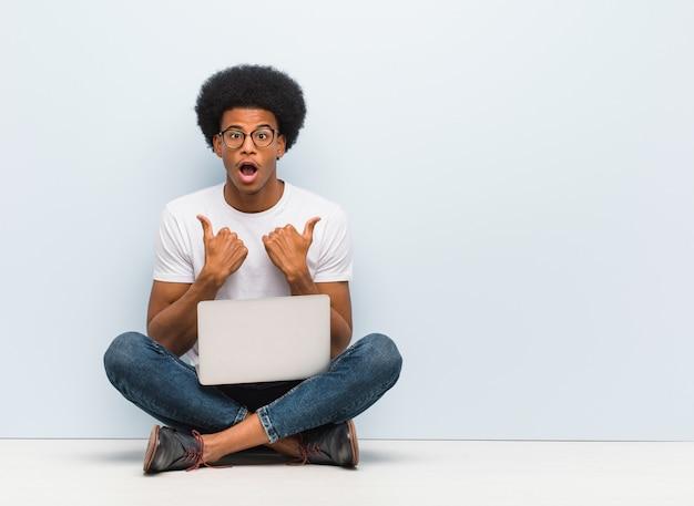 Der junge schwarze mann, der auf dem boden mit einem laptop überrascht sitzt, fühlt sich erfolgreich und wohlhabend Premium Fotos