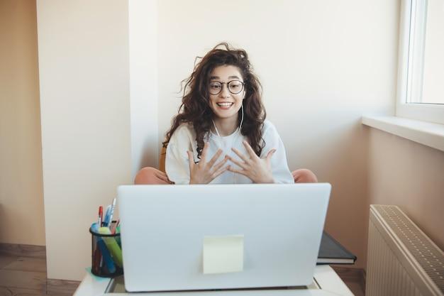 Der junge student mit den lockigen haaren im online-unterricht trägt eine brille und kopfhörer, die sich vor dem laptop ausdrücken Premium Fotos