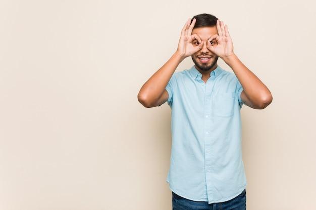 Der junge südasiatische mann, der okay zeigt, unterzeichnen vorbei augen Premium Fotos