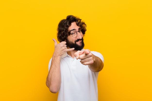 Der junge verrückte mann, der nett lächelt und auf kamera zeigt, während sie anrufen, gestikulieren später und sprechen auf telefongelbwand Premium Fotos