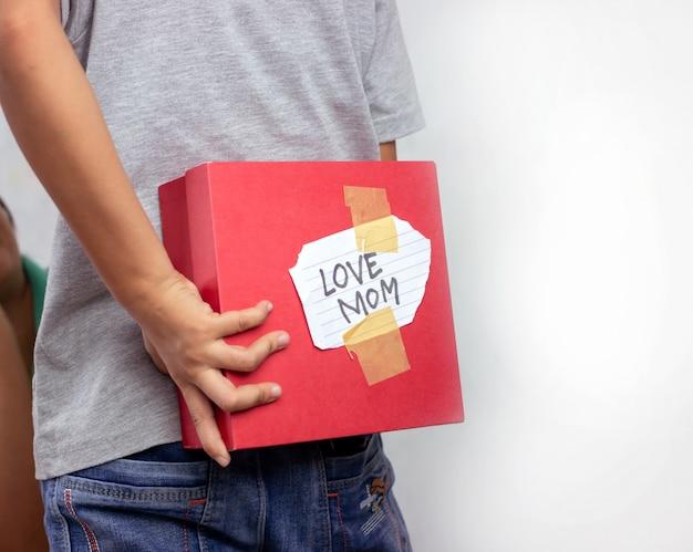 Der junge versteckt auf dem rücken seiner mutter eine geschenkbox. Premium Fotos