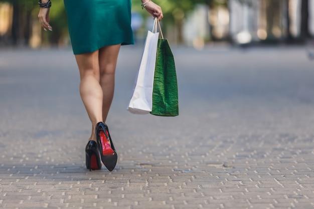 Der jungen frau einkaufstaschen tragen, während sie auf der straße. sexy beine der frau mit handtasche. Premium Fotos