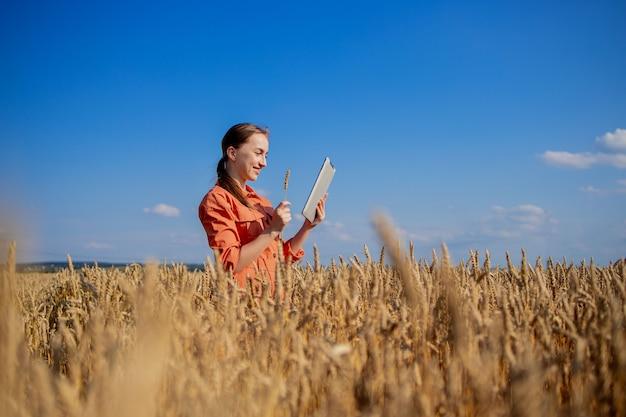 Der kaukasische agronom überprüft das getreidefeld und sendet daten von der tablette an die wolke. konzept für intelligente landwirtschaft und digitale landwirtschaft. erfolgreiche produktion und anbau von bio-lebensmitteln. Premium Fotos