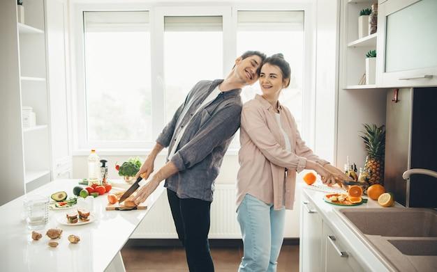 Der kaukasische mann und seine frau bereiten essen in der küche zu, lächeln und genießen die gemeinsame zeit Premium Fotos