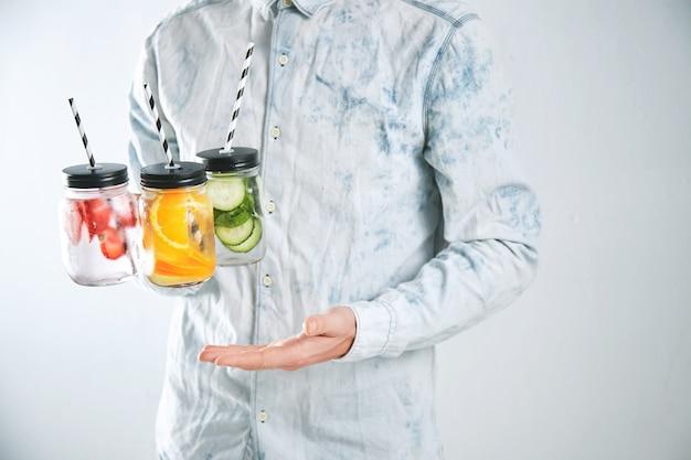 Der kellner hält drei kalte erfrischungsgetränke aus erdbeere, orange, limette, minze, gurke, eis und mineralwasser in rustikalen gläsern mit trinkhalmen Kostenlose Fotos