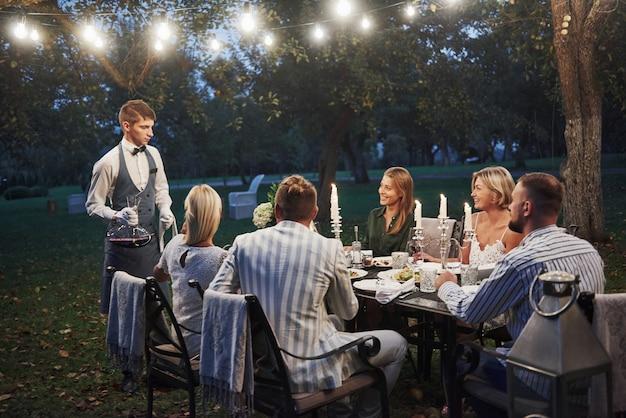 Der kellner mit wein ist hier. freunde treffen sich am abend. schönes restaurant außerhalb Premium Fotos