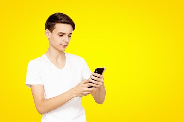 Der kerl im weißen t-shirt mit dem telefon auf einem gelben hintergrund. junger teenager in sozialen netzwerken, das konzept der modernen technologie vorgeschrieben Premium Fotos