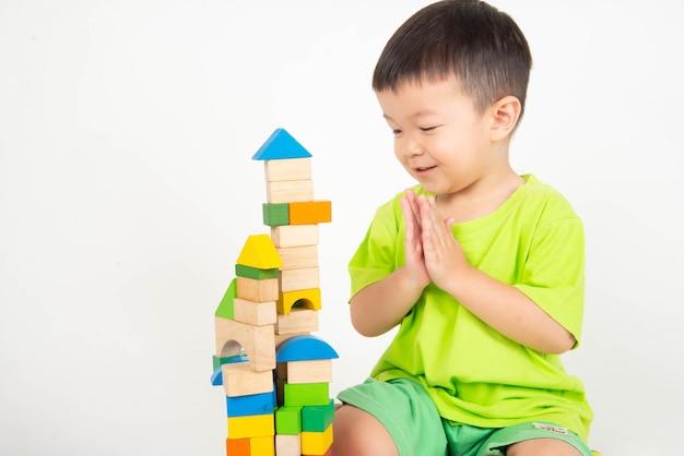 Der kleine asiatische kleinkindjunge, der hölzerne blöcke spielt, tragen sturzhelmingenieur Premium Fotos