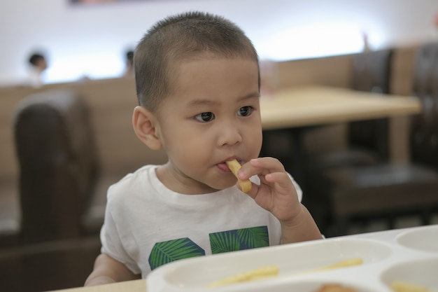 Der kleine junge aß glücklich zu mittag. glücklich eine familienzeit. Premium Fotos