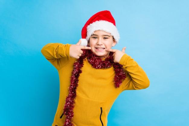 Der kleine junge, der den weihnachtstag lokalisiert trägt einen sankt-hut feiert, lächelt und zeigt finger auf mund. Premium Fotos